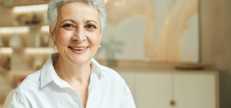 Indoor shot of attractive successful middle aged businesswoman with short gray hair working at her office, posing against stylish interior background. People, age, job and profession concept